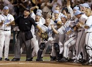 Umpire Tony Walsh holds back celebrating North Carolina players who are waiting by home plate to greet Chad Flack, who hit the go-ahead, two-run home run against Fresno State in the eighth inning of a College World Series game Saturday in Omaha, Neb. North Carolina beat Fresno State, 4-3, to force a rematch at 6 tonight.