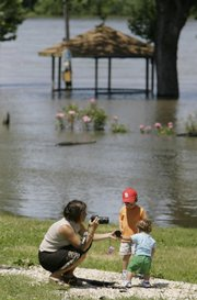 Tonya Sheppard photographs her two sons Will and Brady on Sunday in a park near the floodwaters of the Mississippi River in Louisiana, Mo.