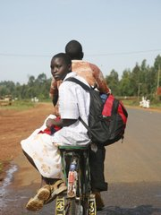 A schoolgirl rides on bicycle taxi in Bungoma, Kenya. Schoolchildren have been targeted and seized by rebel militias, and then thrown into torture centers during an army crackdown in the Mount Elgon area.