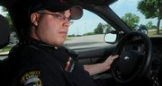 Kansas University patrol officer Todd Carpenter cruises around the residence halls on Daisy Hill during a morning patrol in this July 2008 file photo. KU Public Safety officers are aided in their patrols by security cameras placed throughout campus.