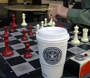 Men play chess over a cup of Starbucks coffee Tuesday in Alameda, Calif. Starbucks Corp. said Tuesday it would close 600 company-operated U.S. stores in the next nine months.