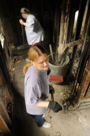 Shannan McCawley and her sister Tonya Beard clean out a closet filled with burned insulation.