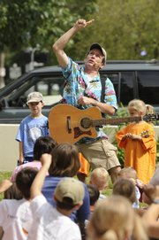"Jim Cosgrove, nationally known children&squot;s musician ""Mr. Stinky Feet,"" entertains more than 500 children and parents Thursday outside the Lawrence Public Library, 707 Vt."