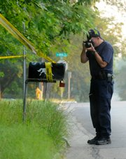 Around 6 a.m. on Friday, Lawrence Police Officers gather evidence at a home at 409 Michigan where the body of Jana Lynne Mackey, a 25-year-old Kansas University student, was found late Thursday night.