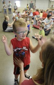 "Curtis Lister, 4, works with Kris Pederson on singing ""The Bus Song"" at the Sertoma-Schiefelbusch Communication Camp on Monday at the Douglas County 4-H Fairgrounds. Curtis is one of dozens of area youths who are honing their communication and social skills at the two-week camp."