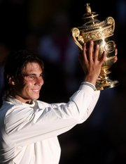 Spain's Rafael Nadal holds his trophy aloft after defeating Switzerland's Roger Federer in the men's singles final. Nadal denied Federer a record sixth-straight Wimbledon title on Centre Court on Sunday in Wimbledon, England.