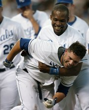 Kansas City's David DeJesus, front, is congratulated by Jose Guillen after DeJesus hit a two-run, walkoff home run in the ninth inning. The home run gave the Royals a 5-4 victory against Seattle on Saturday in Kansas City, Mo.