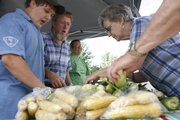 From left, Nolan, 12, and Galen and Marcia Peters, of Lawrence, sell sweet corn during the Lawrence Farmers' Market in the 1000 block of Vermont Street. On the right, Virginia Short, of Lawrence, picks out which ears of corn she wants.