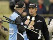 Padraig Harrington, right, and his caddie, Ronan Flood, eat ice cream cones during practice for the British Open on Wednesday in Southport, England.