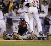 Atlanta Braves catcher Brian McCann sits on the ground after Minnesota Twins' Justin Morneau (33) scored the winning run for the American League in the 15th inning of the MLB All-Star game early Wednesday at Yankee Stadium in New York. Had the game gone another inning, both teams would have been out of pitchers.