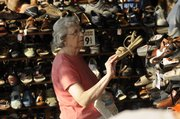 LaFay Brooks, Lawrence, is surrounded by shoes as she shops Thursday in downtown Lawrence during the Sidewalk Sale. Thousands of shoppers swarmed downtown for the annual event.