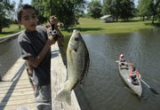 Joni Fuentes, Decatur, Ill., pulls a fish out of the lake Wednesday at the Amazing Grace Bible Camp near Ottawa.