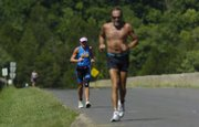 Competitors in the Midwest Mayhem Triathlon run across the Lone Star Lake levee. The event was held Sunday.