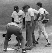 New York Yankees manager Billy Martin, second from left, watches as umpire Tim McClelland uses home plate to measure pine tar on the bat of Kansas City's George Brett in this file photo from July 24, 1983. Brett used the bat to homer in the ninth inning, apparently giving the Royals the victory, but the bat was declared illegal.