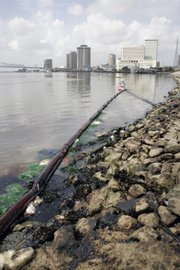 Booms are in place to contain a fuel oil spill Friday in the Mississippi River at the Port of New Orleans. Officials are worried that the spill will affect the fragile wetlands downstream.