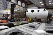 "Workers in Mojave, Calif., prepare the ""mothership,"" an aircraft that will launch a commercial spaceship some 62 miles above Earth. British billionaire Sir Richard Branson and American aerospace designer Burt Rutan are due Monday to show off this mothership called White Knight Two."