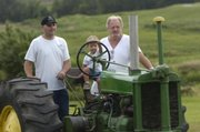 On the left, Bo Enright helps his two-year-old son, Ethan Enright, onto an antique tractor at his Wellsville home. Bo Enright's enthusiasm for tractor pulling as a teenager helped convince his father, Steve Enright, right, to get into the sport.