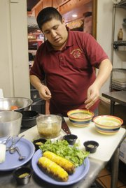 Angel Alvarez, who owns Tortas Jalisco, 534 Frontier Road, works on one of three salsas he will prepare at the Lawrence Farmers' Market on Saturday.