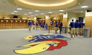 Visitors pass by the giant Jayhawk on the carpet of the locker room Wednesday during an open house tour of the Anderson Family Football Complex.