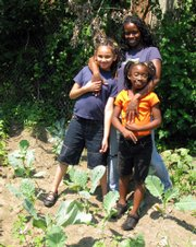 Tanika Gentry, with daughters Natasha, 10, and Queene, 6, grows her own vegetables in the Bushwick section of Brooklyn. Gentry is part of a burgeoning movement of gardeners raising their own fruits and vegetables in response to rising prices.