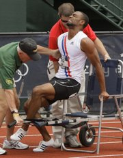 Tyson Gay is helped to a wheelchair after falling during a quarterfinal heat of the men's 200-meter race July 5 at the U.S. Olympic Track and Field Trials in Eugene, Ore.