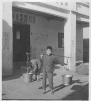 Ray Chao would carry water buckets a mile to a water source while growing up in a Chinese village in this 1971 photo. His sister is shown in the background, at left.