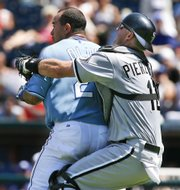 Kansas CIty's Miguel Olivo, left, is restrained by White Sox catcher A.J. Pierzynski as Olivo charges the mound in the fifth inning. The Royals beat the White Sox, 14-3, Sunday in Kansas City, Mo.