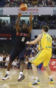 LeBron James, left, looks to pass against Australia's Mark Worthington. The U.S. men's basketball team won, 87-76, in a warmup game for the Olympics on Tuesday in Shanghai, China.