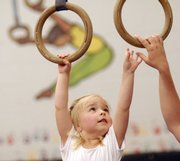 Elena Heatwole, 3, reaches to grasp a set of rings during a children's class at the East Lawrence Parks and Recreation Center, 1245 E. 15th St.