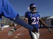 KU safety Darrell Stuckey high-fives a fan in this Nov. 17, 2007, file photo of pregame warmups before Kansas faced Iowa State at Memorial Stadium.