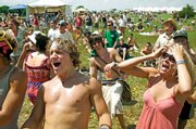 Damian Conrad-Davis, left, of Lamoni, Iowa, and Abby Hernandez, right, of Kansas City, Mo., sing along to State Radio on June 7 at the Wakarusa Music and Camping Festival at Clinton Lake. Festival organizer Brett Mosiman has accused the Kansas Department of Wildlife and Parks of discriminating against the 'hippie' crowd that attends the event by charging more, and he said the music festival may not return to Clinton State Park as a result.