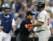 Kansas City's John Buck, left, and plate umpire Alfonso Marquez, center, keep Minnesota's Delmon Young from charging the mound after Zack Greinke hit him with a pitch. The Twins defeated the Royals, 7-3, on Saturday in Kansas City, Mo.