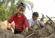 Allen Meyer, 9, left, and his brother, Trysten, 11, pack the sides of a mud fort that they and others built Tuesday along the Kansas River north of Constant Park, near Sixth and Tennessee streets. Lawrence children and their parents joined forces in the morning to re-create the fort, a common structure that pioneers and Civil War-era troops used as a lookout and for security. About two dozen youngsters participated in building two mud forts.
