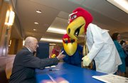 Hal Sandy autographs postcards with a couple of Jayhawk mascots in this 2005 photo courtesy of University Relations.