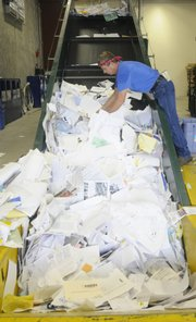 Tom Schmitendorf, who works at KU's Recycling Center on West Campus, sorts through papers ready to be bundled.