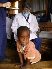 Dr. Steve Segebrecht, Lawrence, completes paperwork after treating a young boy in Kenya in 2008.