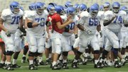 Kansas quarterback Todd Reesing and his offensive line from left, Matt Darton, Chet Hartley, Ryan Cantrell, Adrian Mayes and Jeff Spikes, break from the huddle at open practice on Friday at Memorial Stadium. Kansas coach Mark Mangino named Spikes, who will replace departed left tackle Anthony Collins, the starter for the 2008 season at left tackle.
