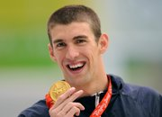 Michael Phelps shows his seventh gold medal after the men's 100-meter butterfly final today in Beijing.
