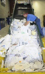 Tom Schmitendorf, who works at Kansas University's Recycling Center on West Campus, sorts through papers ready to be bundled. KU did not receive exemplary status on a recent report card of green initiatives at state colleges and universities, but officials say that may simply be due to incomplete paperwork on a survey.