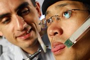 Maysam Ghovanloo, assistant professor at Georgia Tech, points to a tiny magnet on graduate student Xueliang Huo's tongue in Atlanta. The device will turn Huo's tongue into a joystick that controls a wheelchair, and the research team developing the process hopes it could help the disabled gain more mobility.