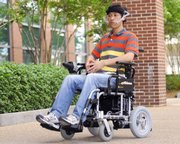 Graduate student Xueliang Huo glides down a walkway in a wheelchair that's controlled by a tiny magnet glued to his tongue. He is helping develop a system that turns the tongue into a joystick that controls wheelchairs and other electronics.