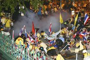 Thai police shoot tear gas into anti-government protesters Friday in Bangkok, Thailand. Police muscled into crowds of anti-government protesters occupying the prime minister's office compound Friday, sparking scuffles that left several people with minor injuries.