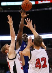 Kansas University's Sherron Collins, center, shoots over the defense of Carleton's Robert Saunders, left, and Aaron Doornekamp. KU beat the Ravens, 84-83, in an exhibition Saturday in Ottawa, Ontario.
