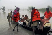 Rescuers help people  to safer areas in Patna, India, on Saturday. A rescue boat filled with flood victims capsized and killed 20 people in northern India, where monsoon flooding grew worse because of heavy rain and water flowing from neighboring Nepal, officials said Saturday.