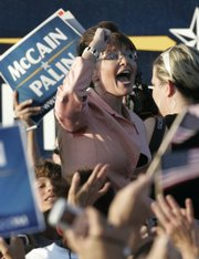 Republican vice presidential candidate, Alaska Gov. Sarah Palin, pumps her fist as she walks toward a bus at a campaign stop Saturday in Washington, Pa.