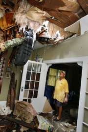 Richard Bezet looks over damage to the living room of his Baton Rouge, La., home after a tree fell through the roof of their house from Hurricane Gustav winds.
