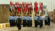 Iraqi security forces carry Iraqi flags during a handover ceremony parade Monday at the government headquarters in Ramadi, capital of Anbar province, in Iraq. The U.S. military handed over control of the once brutally violent Anbar province to Iraqi forces Monday, marking a major milestone in America's plan to eventually send its troops home, but American officials warned that the struggle against insurgents was not over in the western region.