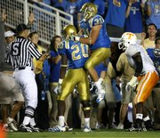 UCLA running back Raymond Carter (20) celebrates with teammate Trevor Theriot after scoring a touchdown in the second half. UCLA defeated No. 18 Tennessee, 27-24, in overtime on Monday in Pasadena, Calif.