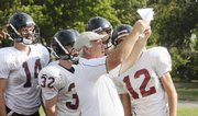 Lawrence high assistant coach Don Durkin shows some Lions players the next play to run Tuesday at practice.