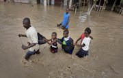A man leads children through a flooded street Wednesday after Hurricane Hanna hit the area in Gonaives, Haiti Three storms have killed at least 126 people in Haiti in less than three weeks.